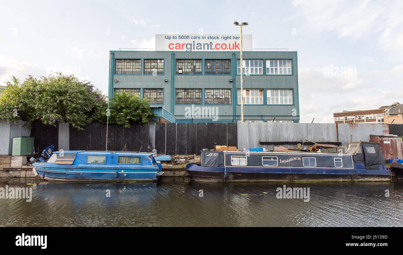 Traditional narrowboats moored on the Grand Union Canal beside the Car Giant industrial unit and warehouses at Old - Stock Image