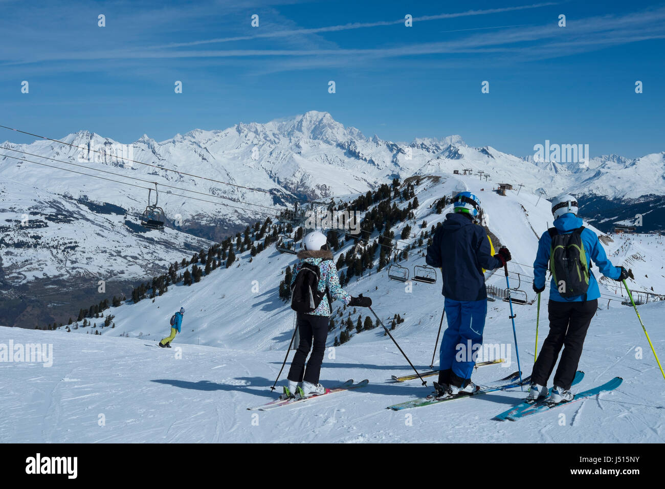 Skiers about to descend to Montchavin les Coches with Mont Blanc in the distance, French alps. Stock Photo
