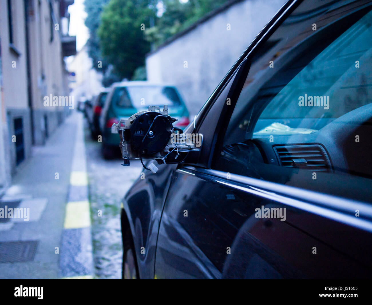 Car with broken mirror parked in the street - Stock Image