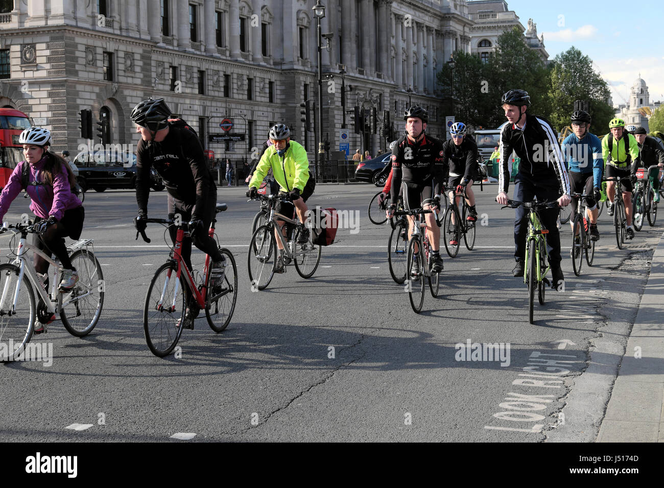 Commuters cyclists leaving work cycling near Parliament Square outside the Houses of Parliament in Westminster, - Stock Image