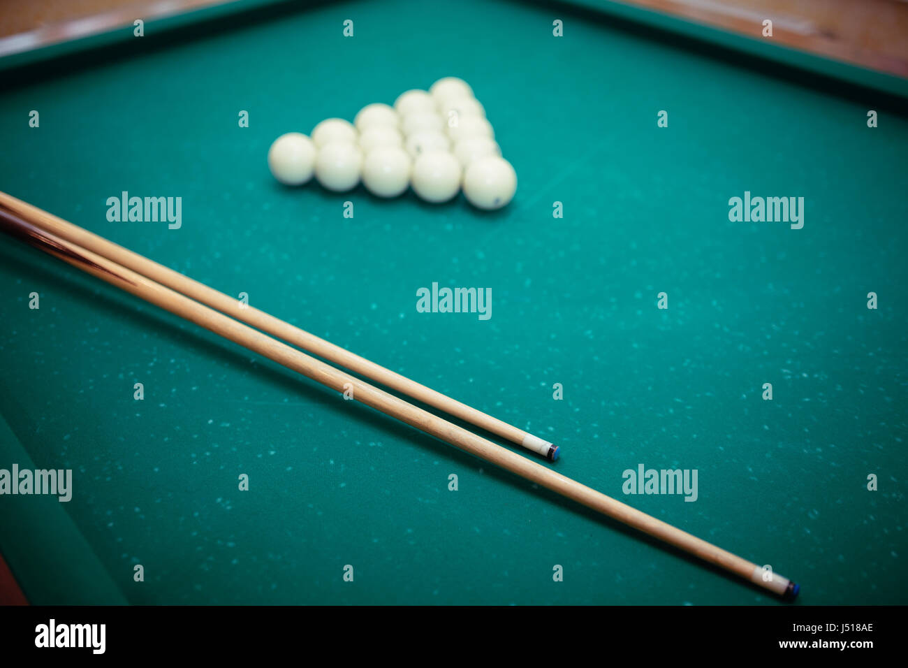 Billiard balls and two Cues in the form of a triangle on the billiard table are ready for the game. - Stock Image