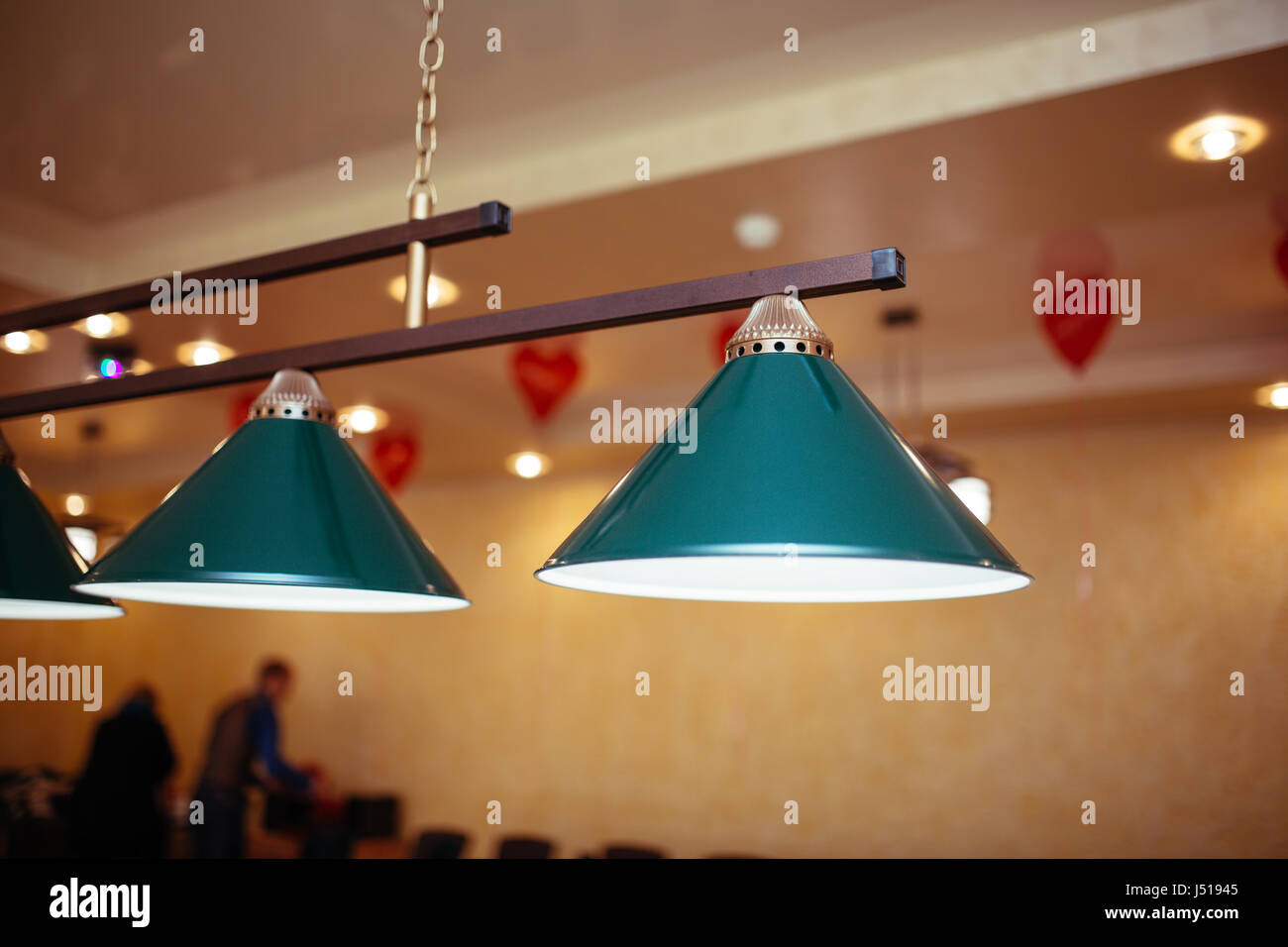 Billiard lamps above the billiard table are ready for the game. - Stock Image