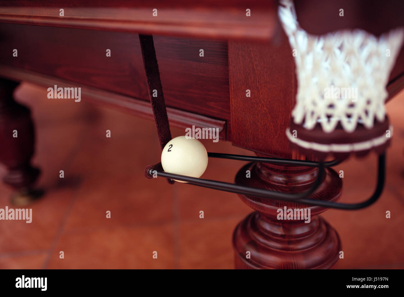 Billiard ball under the pool table in mesh - Stock Image