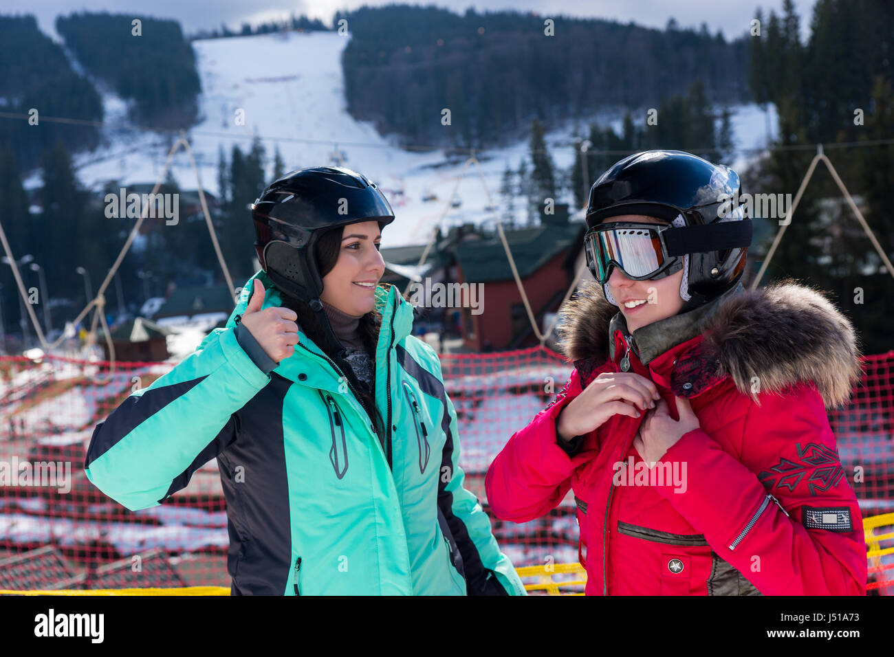 Young women in ski suits, with helmets and ski goggles standing in a ski-resort in winter period - Stock Image