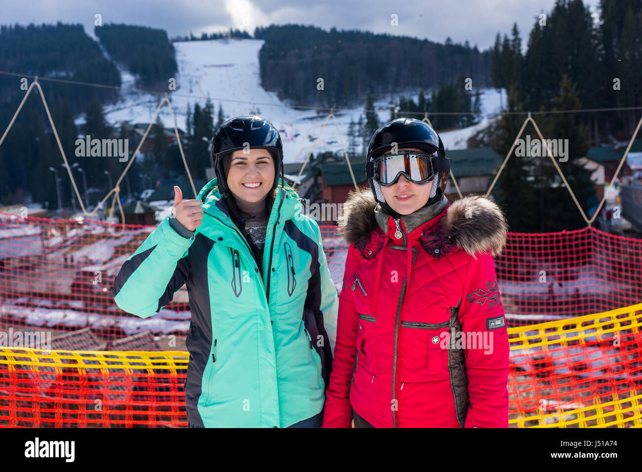Young smiling women in ski suits, with helmets and ski goggles standing in a ski-resort in winter period - Stock Image