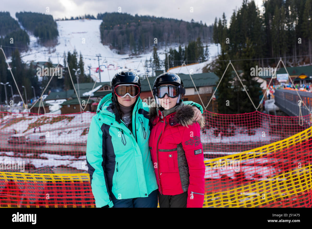 Smiling women in ski suits, with helmets and ski goggles standing in a ski-resort in winter period - Stock Image