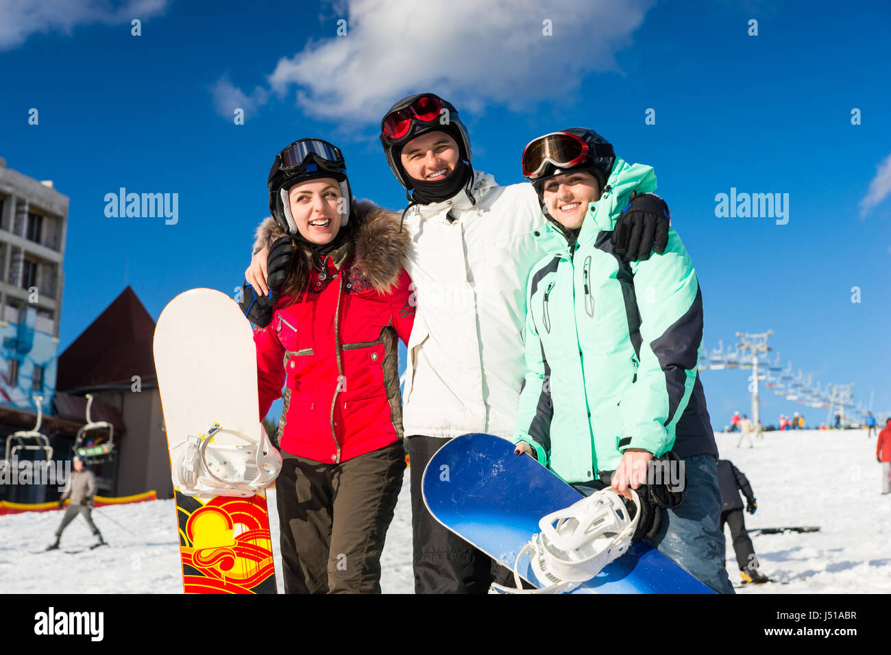 Youth in ski-suits and ski goggles having fun while standing with snowboards in a ski-resort in winter period - Stock Image
