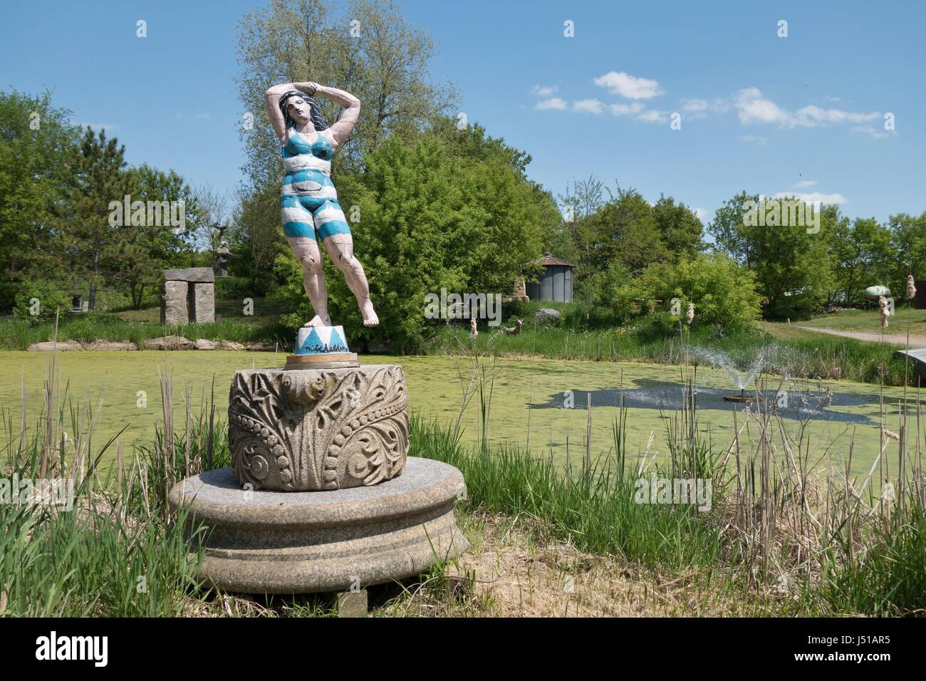 A sculpture of a woman in an old fashioned bathing suit, near a pond, at Big Stone Mini Golf and Sculpture Garden - Stock Image