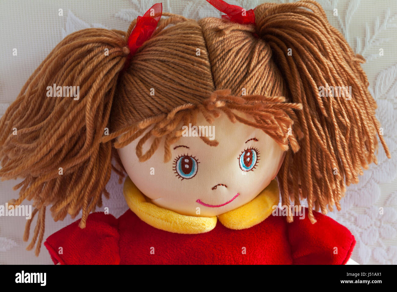Doll with hair tied in pigtails soft cuddly toy - Stock Image