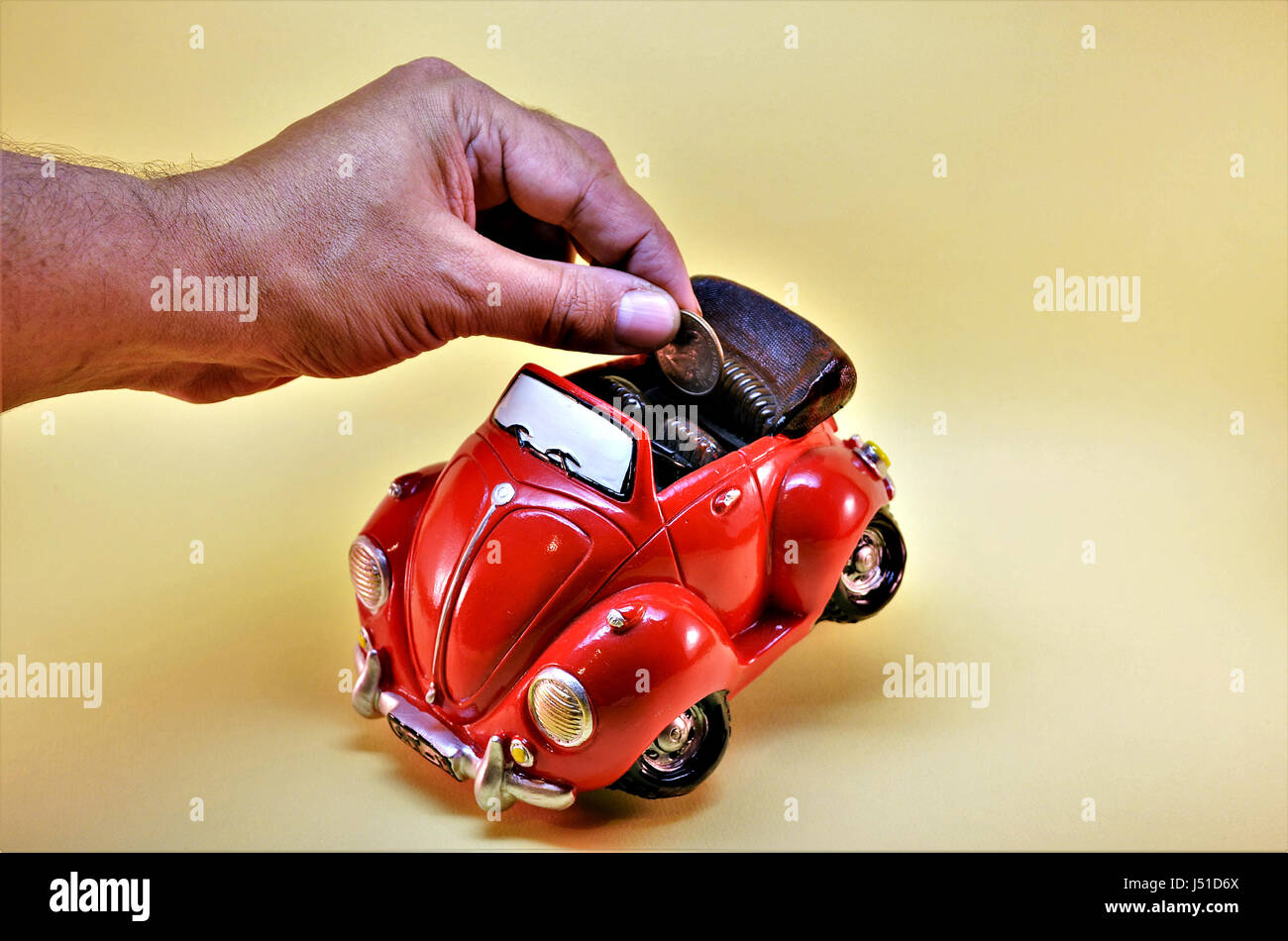 Coin bank. Man putting coin into coin bank. Coin bank child in car shape symbolizing the savings to buy a new car. - Stock Image