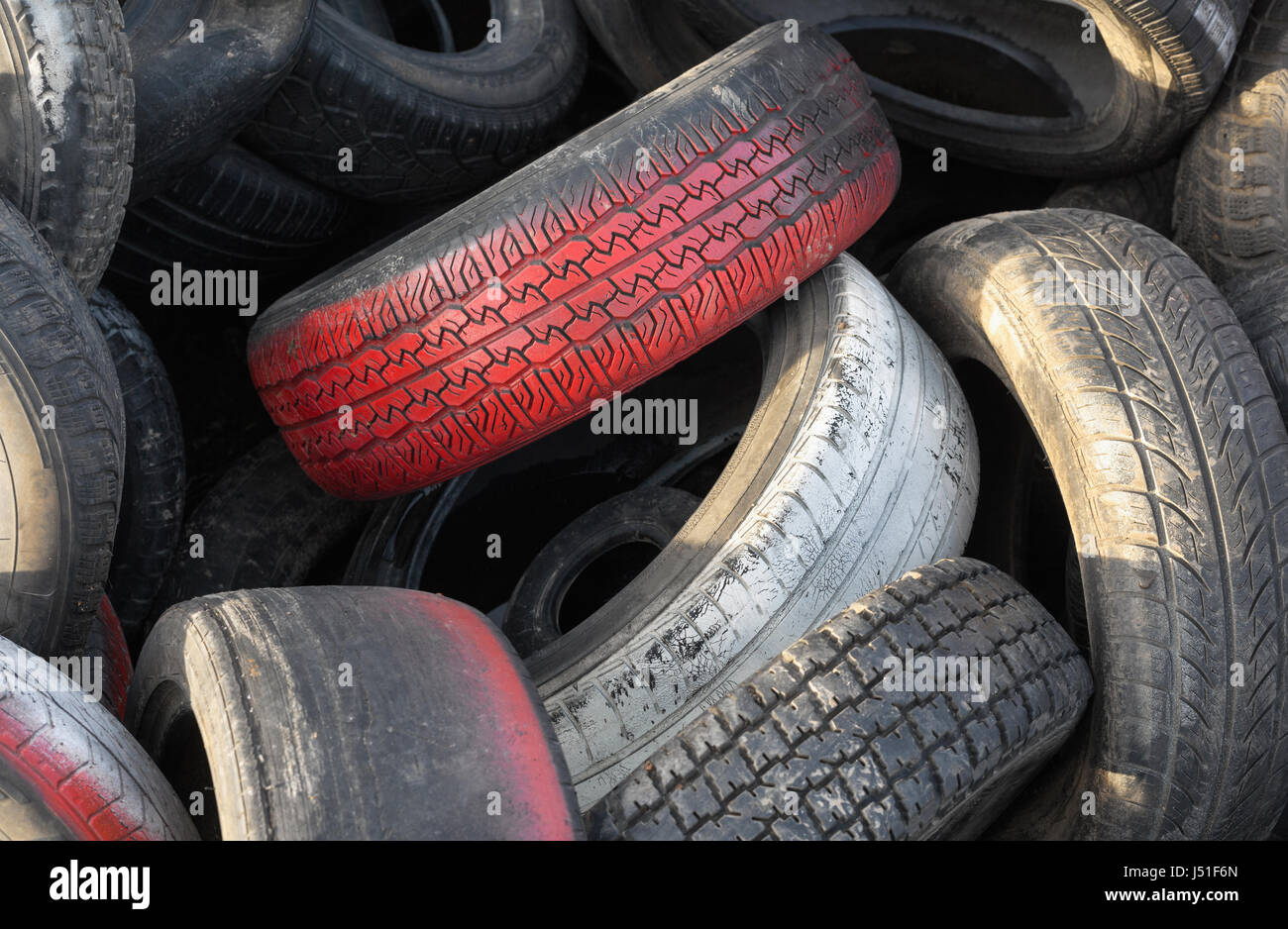 Close up of red car tires with tread in a pile of used tires - Stock Image