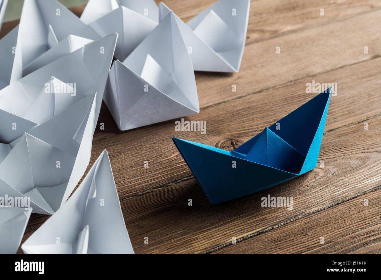 Business leadership concept with white and color paper boats on wooden table - Stock Image
