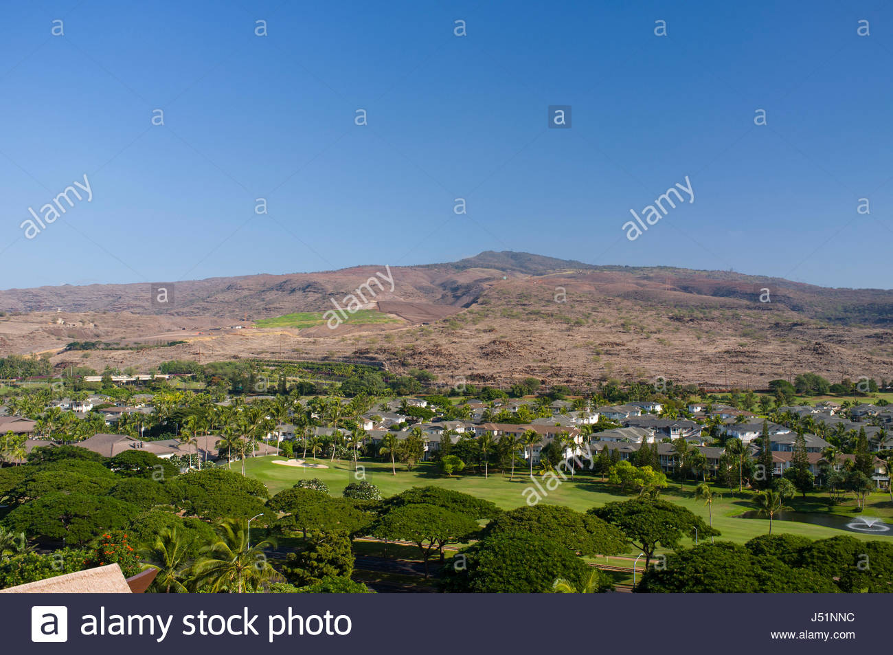 Waimanalo Gulch Landfill in the Waianae Mountains above Kapolei golf course and houses, Kapolei, Oahu, Hawaii, USA - Stock Image