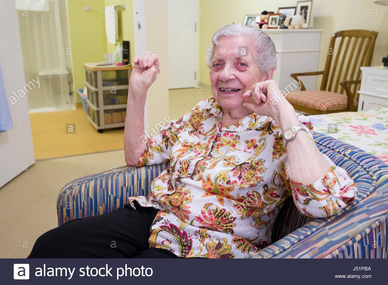 Elderly Caucasian woman sitting in her apartment, Kahala, Honolulu, Oahu, Hawaii, USA - Stock Image