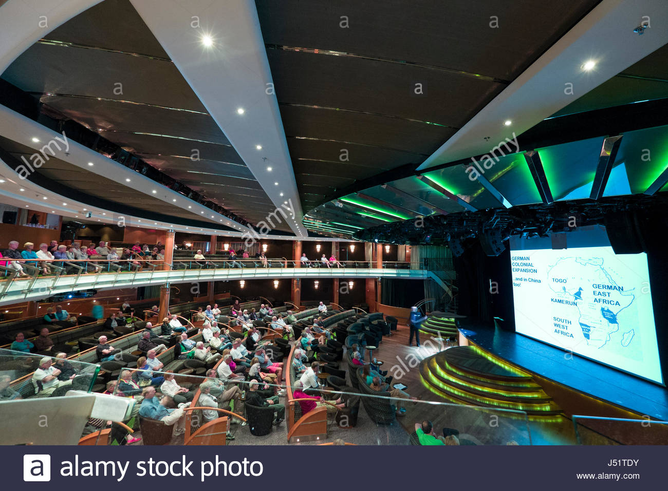 Passengers sitting in the Constellation Theatre aboard the Regent Seven Seas Voyager cruise ship listening to speaker - Stock Image