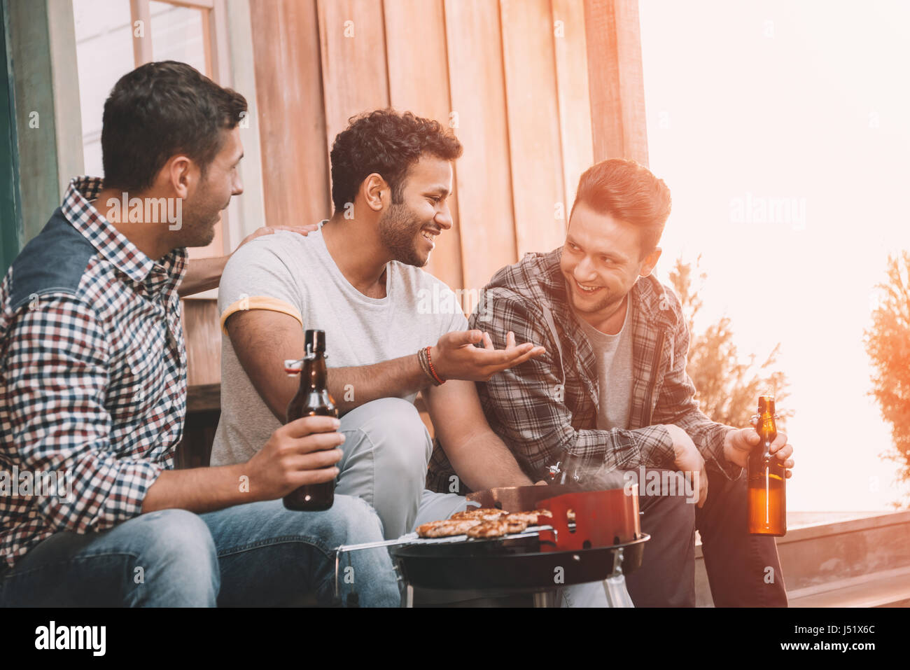 Smiling young friends drinking beer and talking while grilling meat outdoors - Stock Image