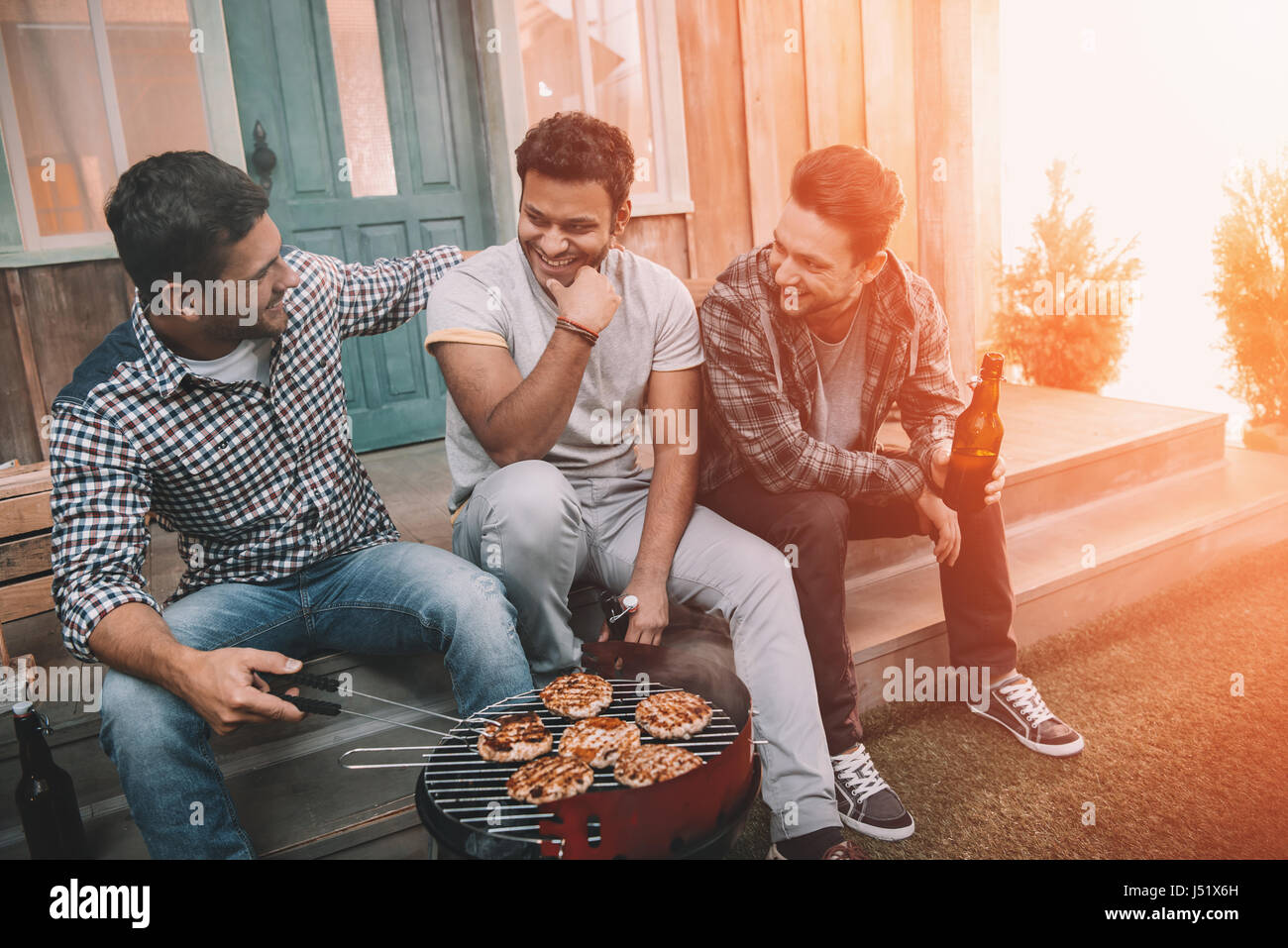 Three young men drinking beer and smiling while sitting on porch and making barbecue - Stock Image