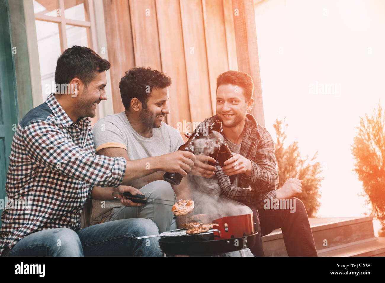 Smiling young men clinking beer bottles and grilling meat on porch - Stock Image