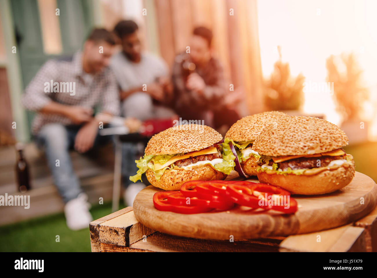 Close-up view of fresh tasty homemade hamburgers on wooden cutting board - Stock Image