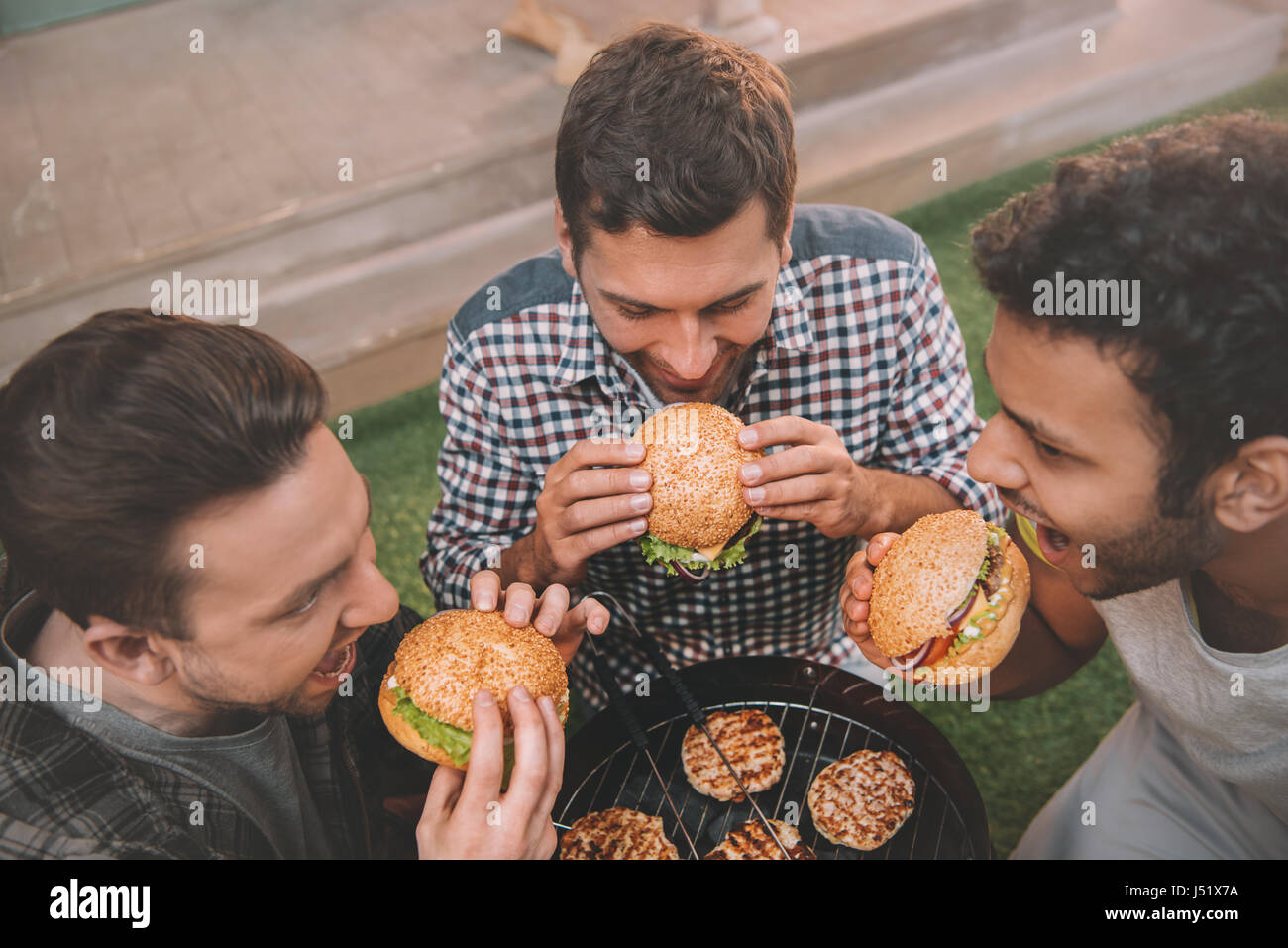 High angle view of three young men eating fresh hamburgers above grill - Stock Image