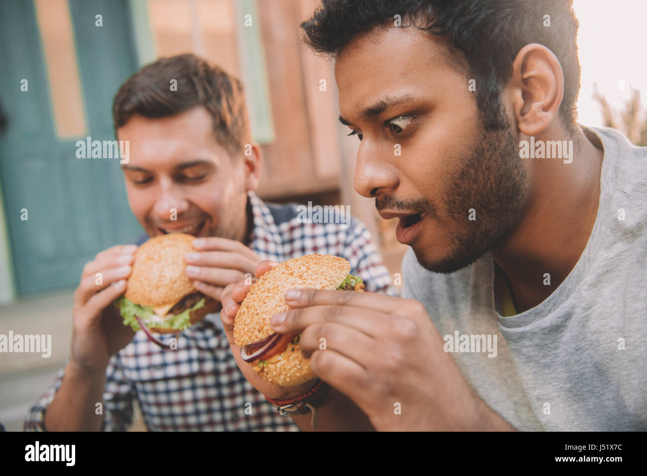 Close-up view of emotional young men eating gourmet hamburgers outdoors - Stock Image