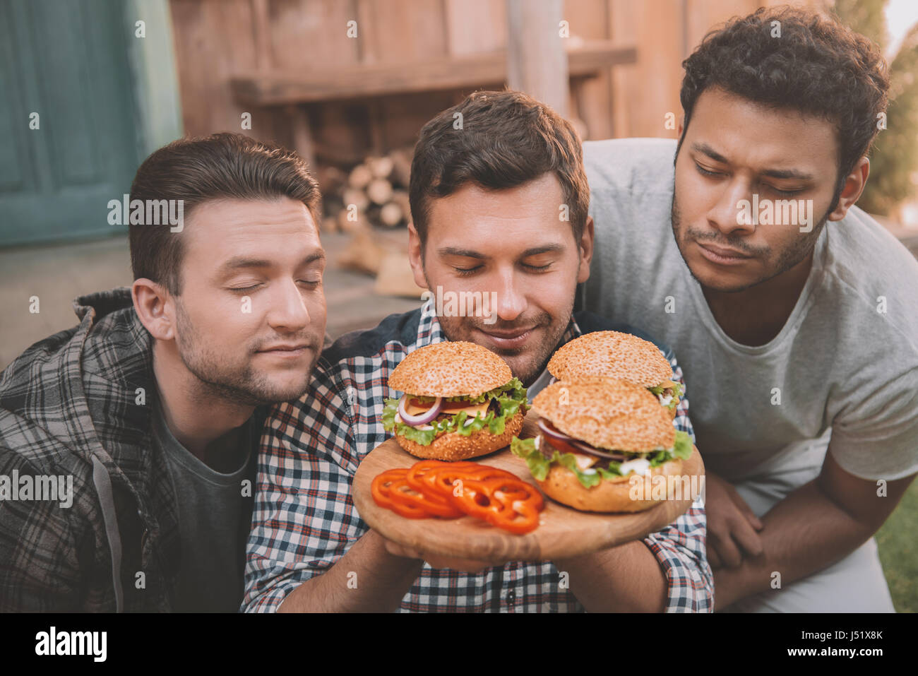 Three young men with closed eyes sniffing fresh homemade hamburgers - Stock Image