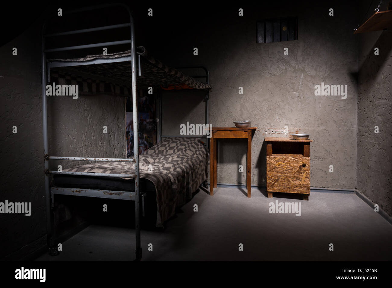 Jail Cell With Iron Bunk Bed And Wooden Bedside Table With Aluminum