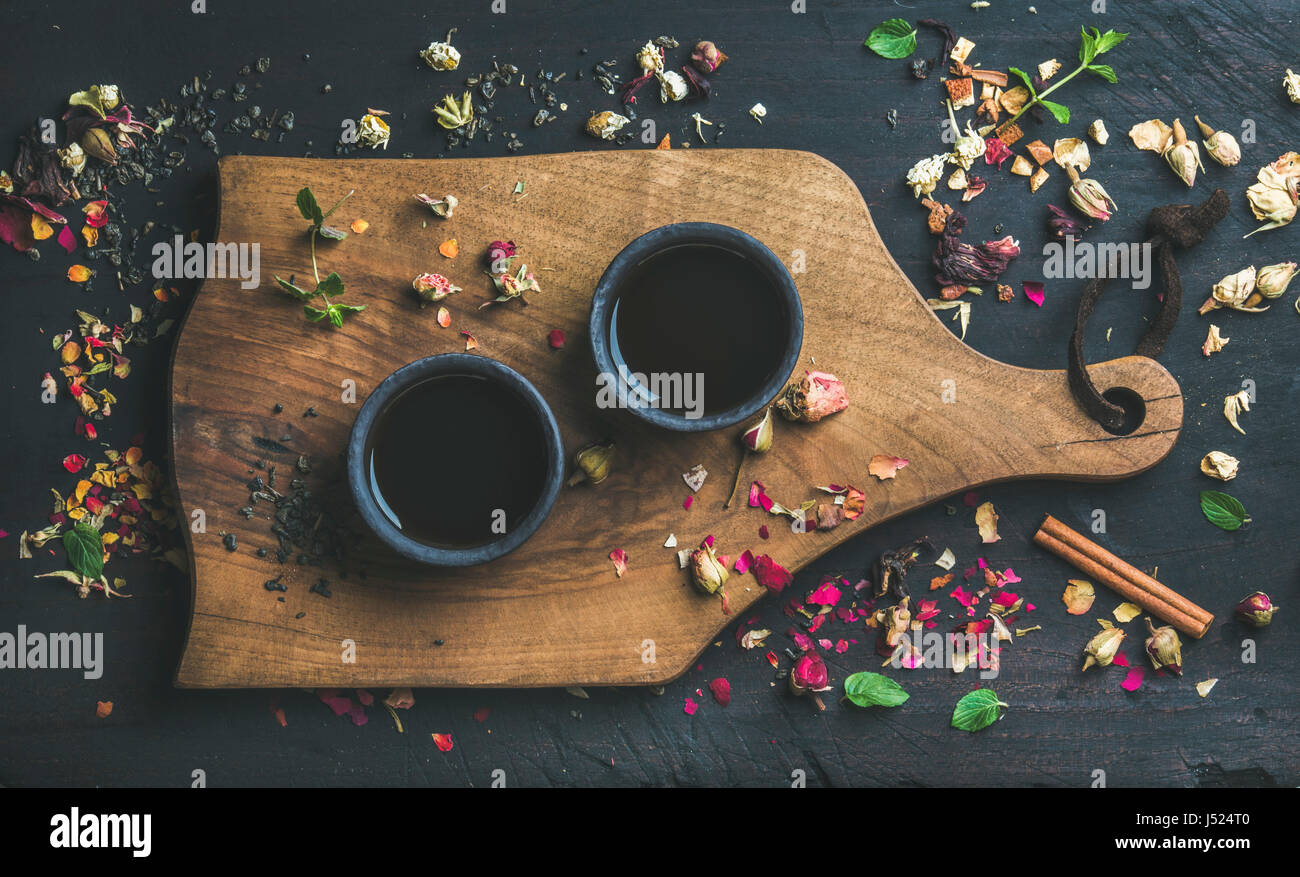 Chinese black tea in black stoneware cups on serving wooden board over black wooden background with herbs, flower - Stock Image