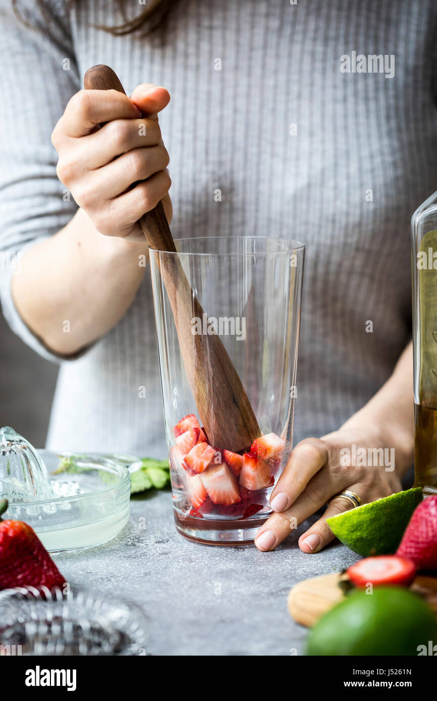 A woman is photographed as she is muddling strawberries to make margaritas. - Stock Image