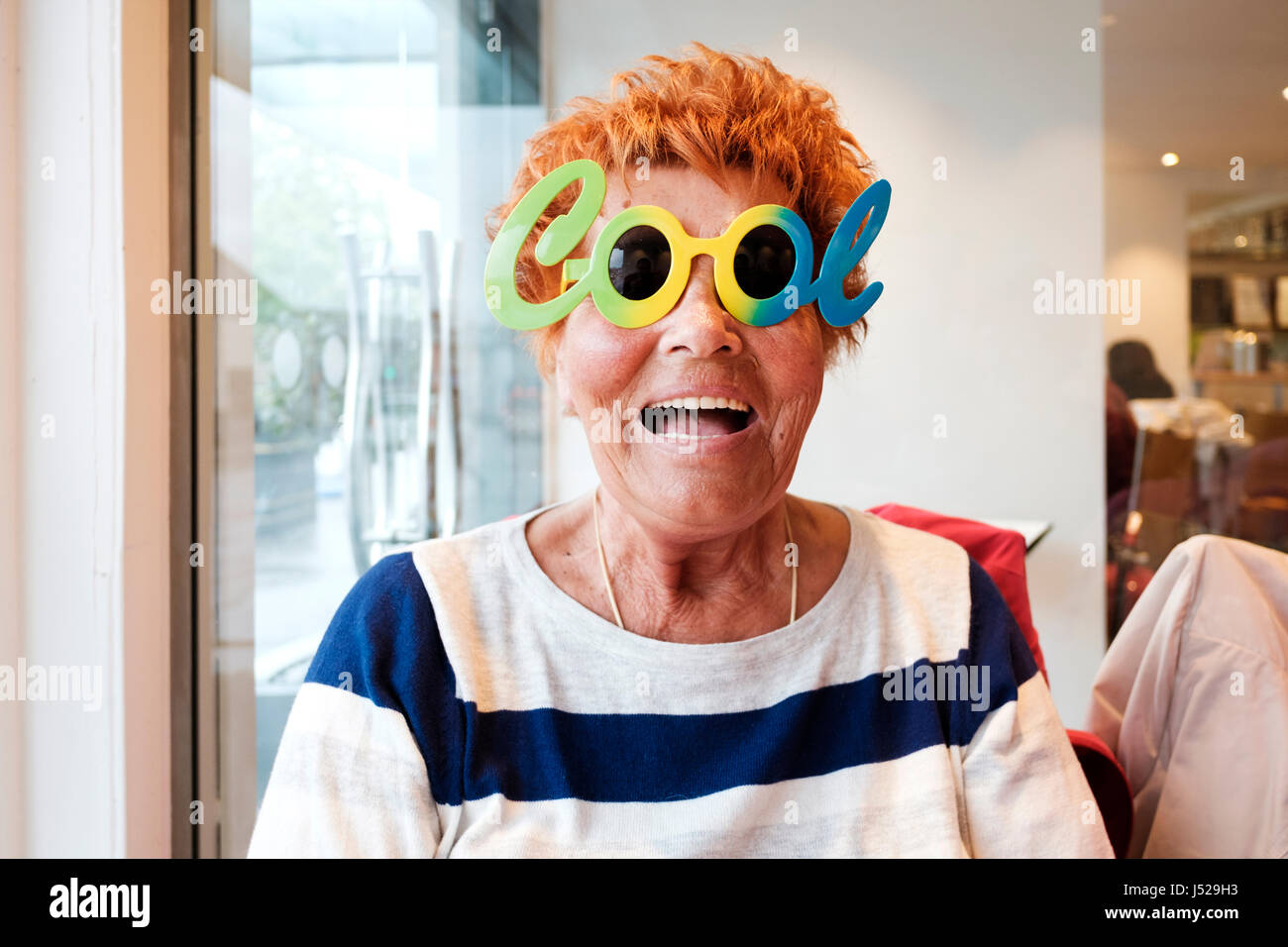An elderly lady or old aged pensioner having a good time and enjoys a fun moment with some comic cool glasses - Stock Image