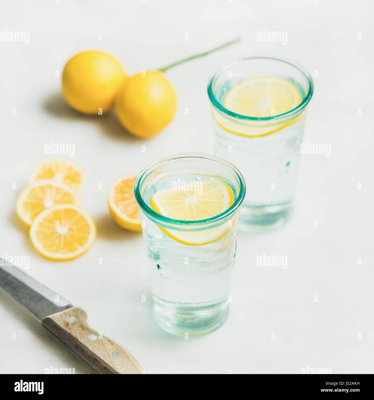 Morning detox lemon water in glasses and fresh lemons over marble background, selective focus, square crop. Clean - Stock Image