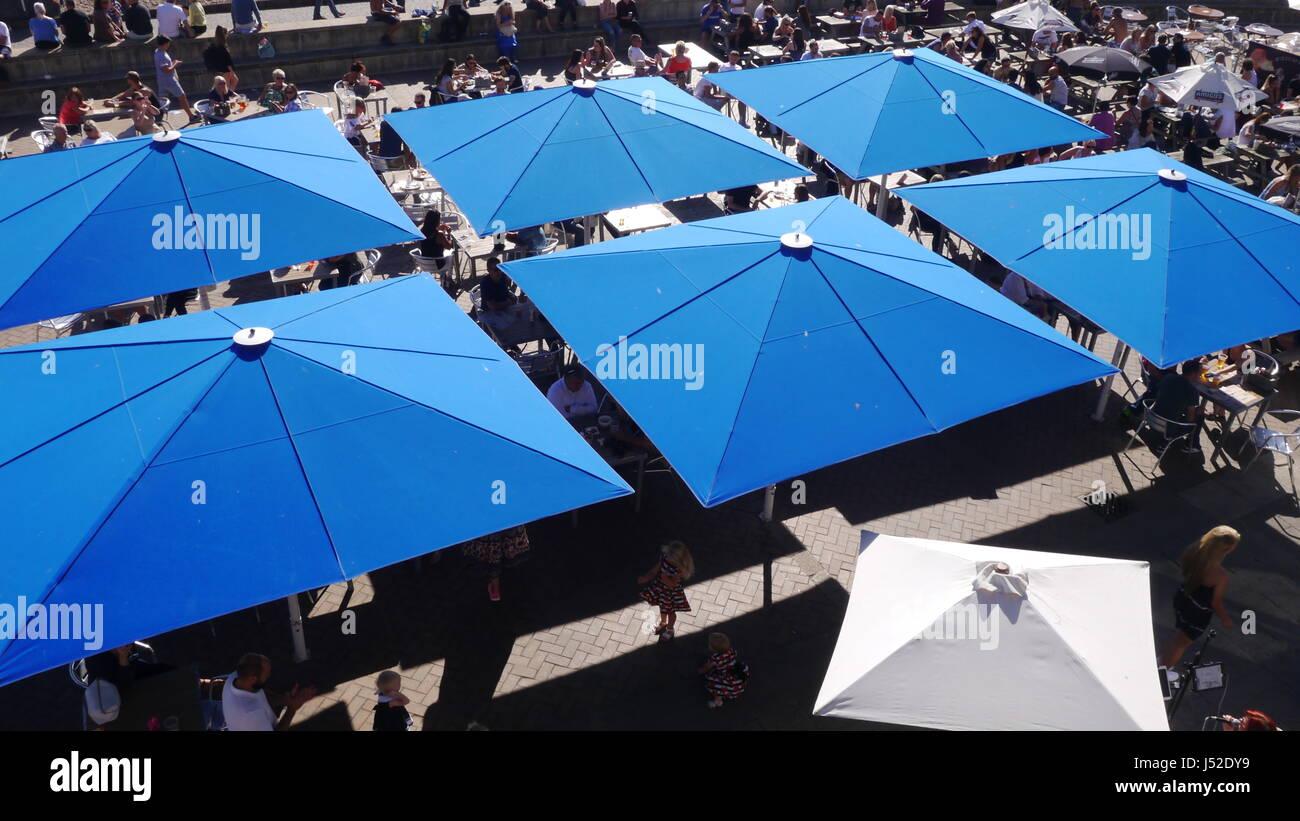 Large blue umbrellas on Brighton seafront, seen from above - Stock Image