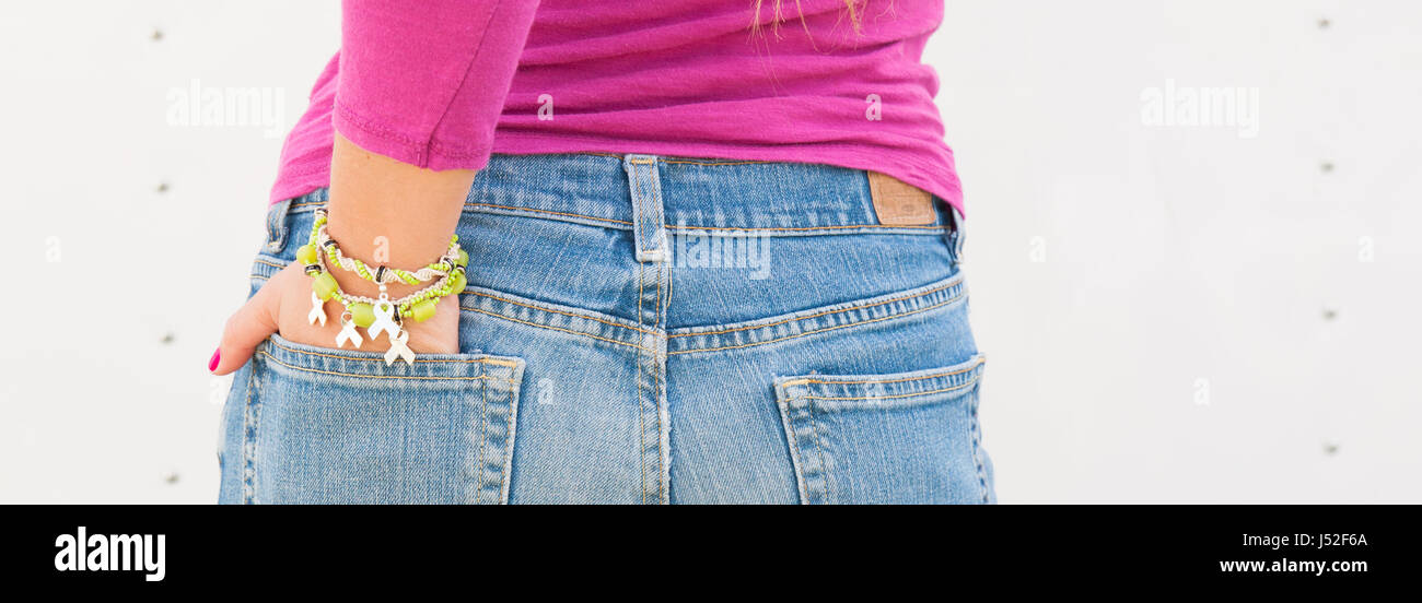 Woman wearing bracelet with awareness ribbon charms. - Stock Image