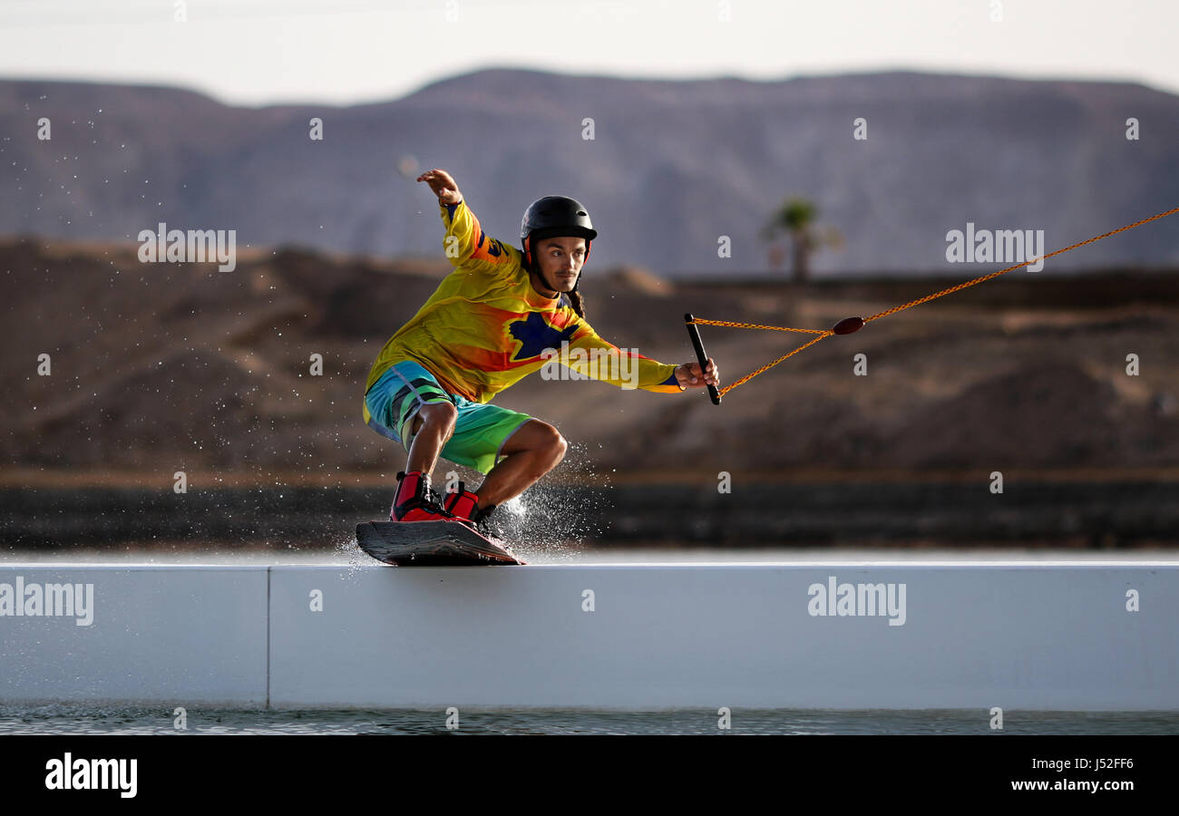 Wakeboarding sportsman rider on the slider in the wake cablepark, active sports and life style, water sport as hobby, - Stock Image