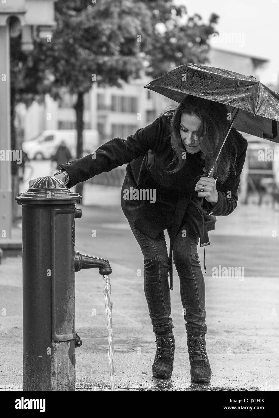 A rainy day in Annecy in black and white a female model with an umbrella by a water fountain - Stock Image