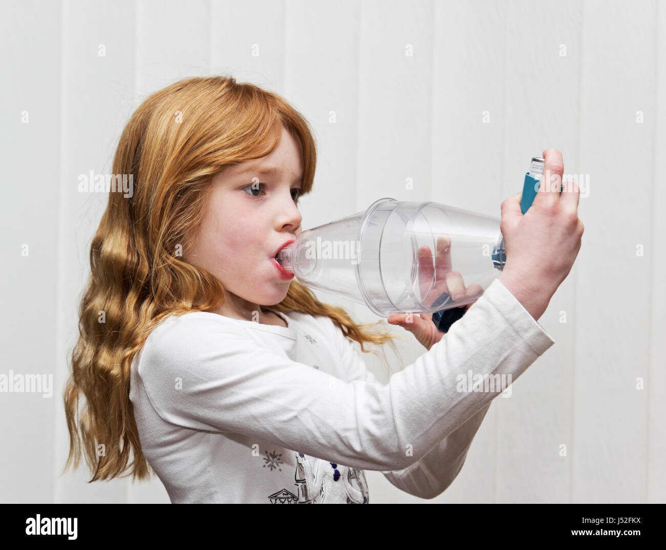A seven year old girl using a Ventolin inhaler with a volumatic spacer device for asthma relief. - Stock Image