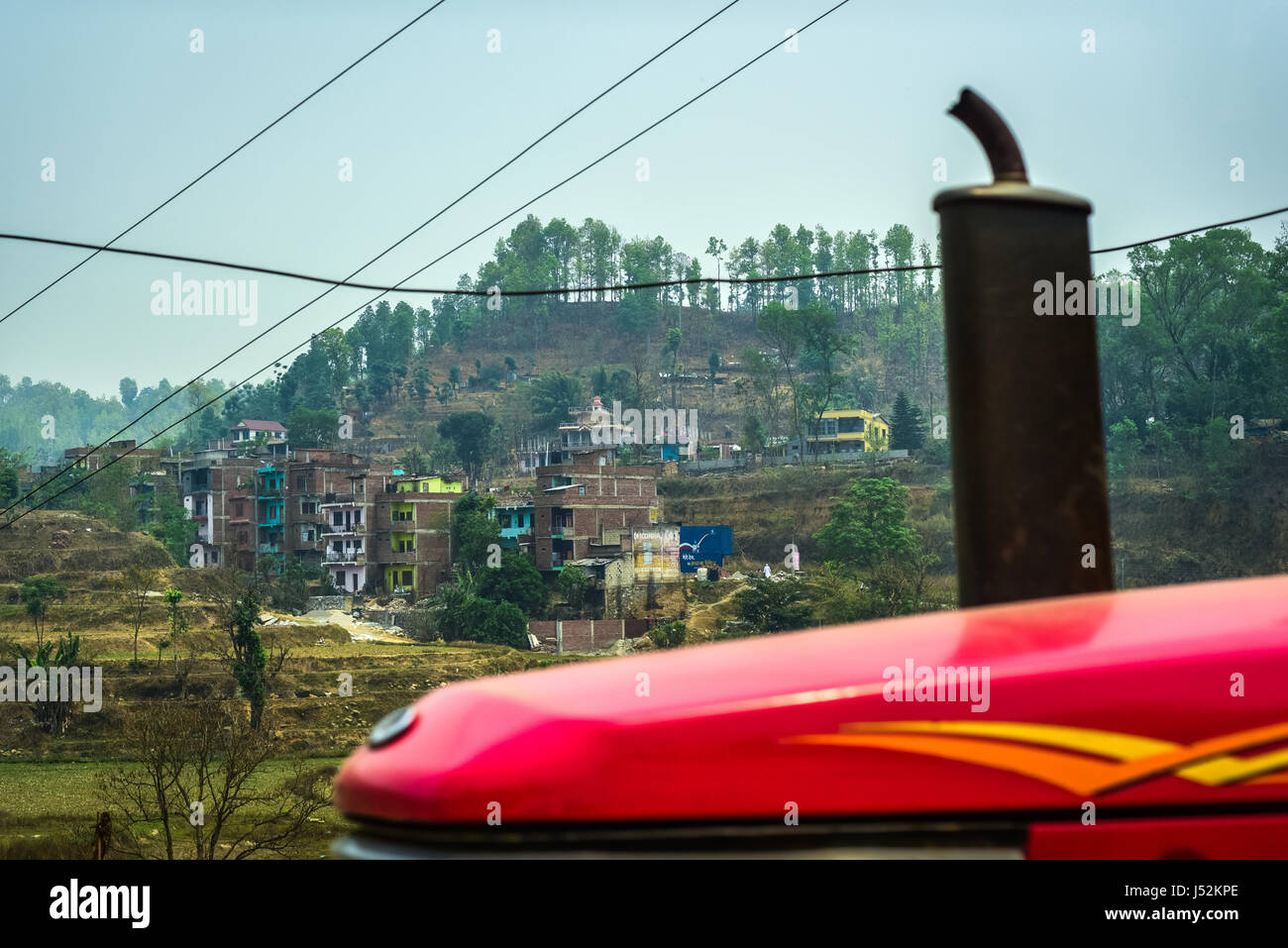 Nepali countryside with a smoke stack of a truck and power lines. - Stock Image