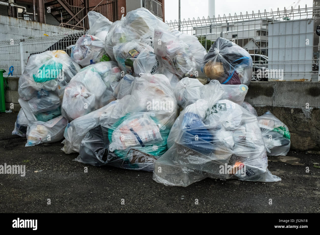 Plastic rubbish bags in a car park waiting to be collected in Tokyo - Stock Image