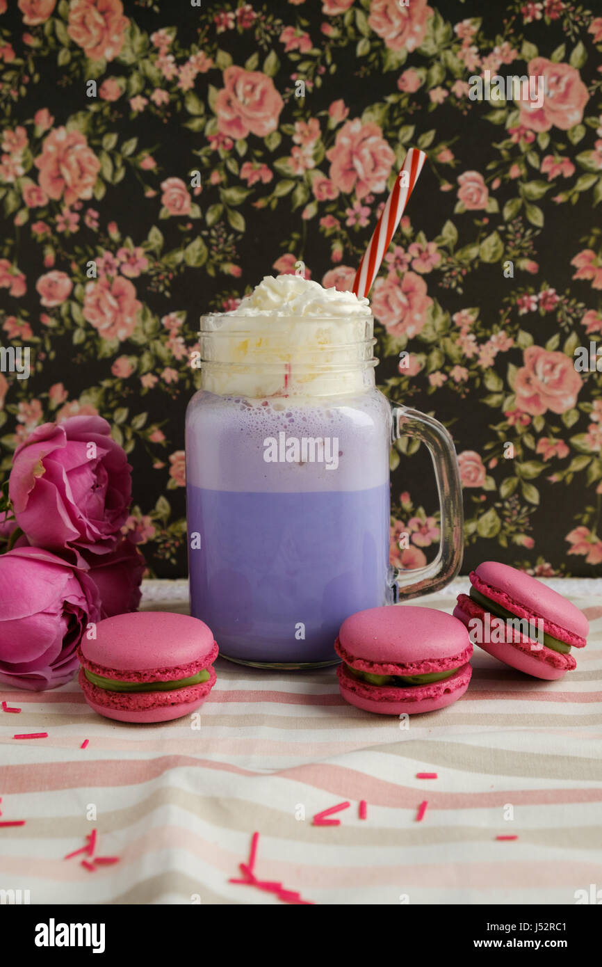 Purple coffee in stylized mason jar cup with macarons and roses and colorful decoration on background of floral - Stock Image