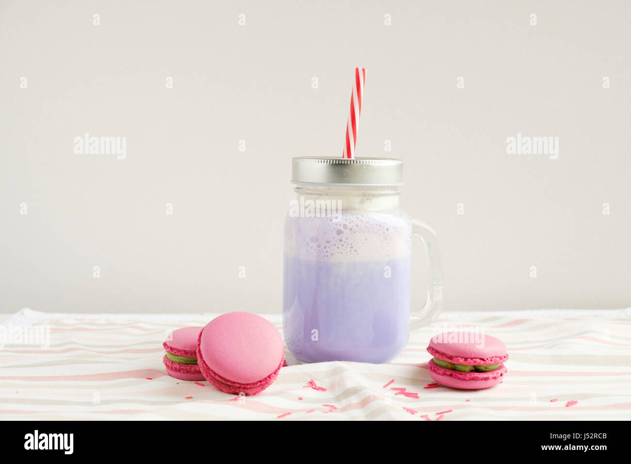 Purple coffee in stylized mason jar cup with macarons and colorful decoration. Blueberry milk shake, cocktaill, - Stock Image