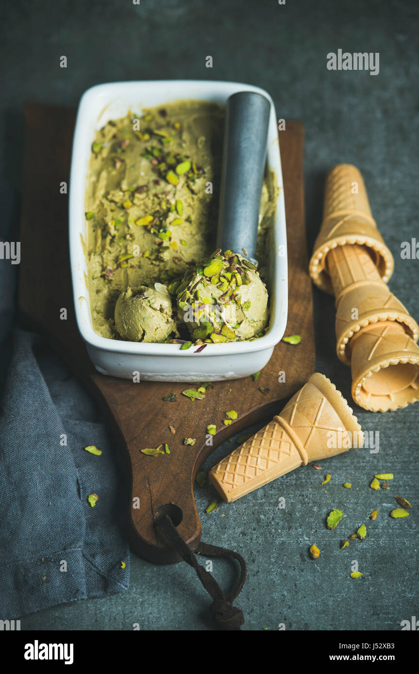 Homemade pistachio ice cream in ceramic mold with metal scooper, crashed pistachio nuts and waffle cones over dark - Stock Image