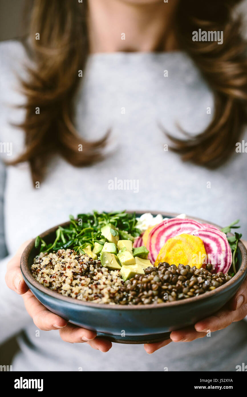 A woman wearing a gray shirt is holding an abundance bowl made up of quinoa, sprouts, lentils, avocados, and chioggia - Stock Image