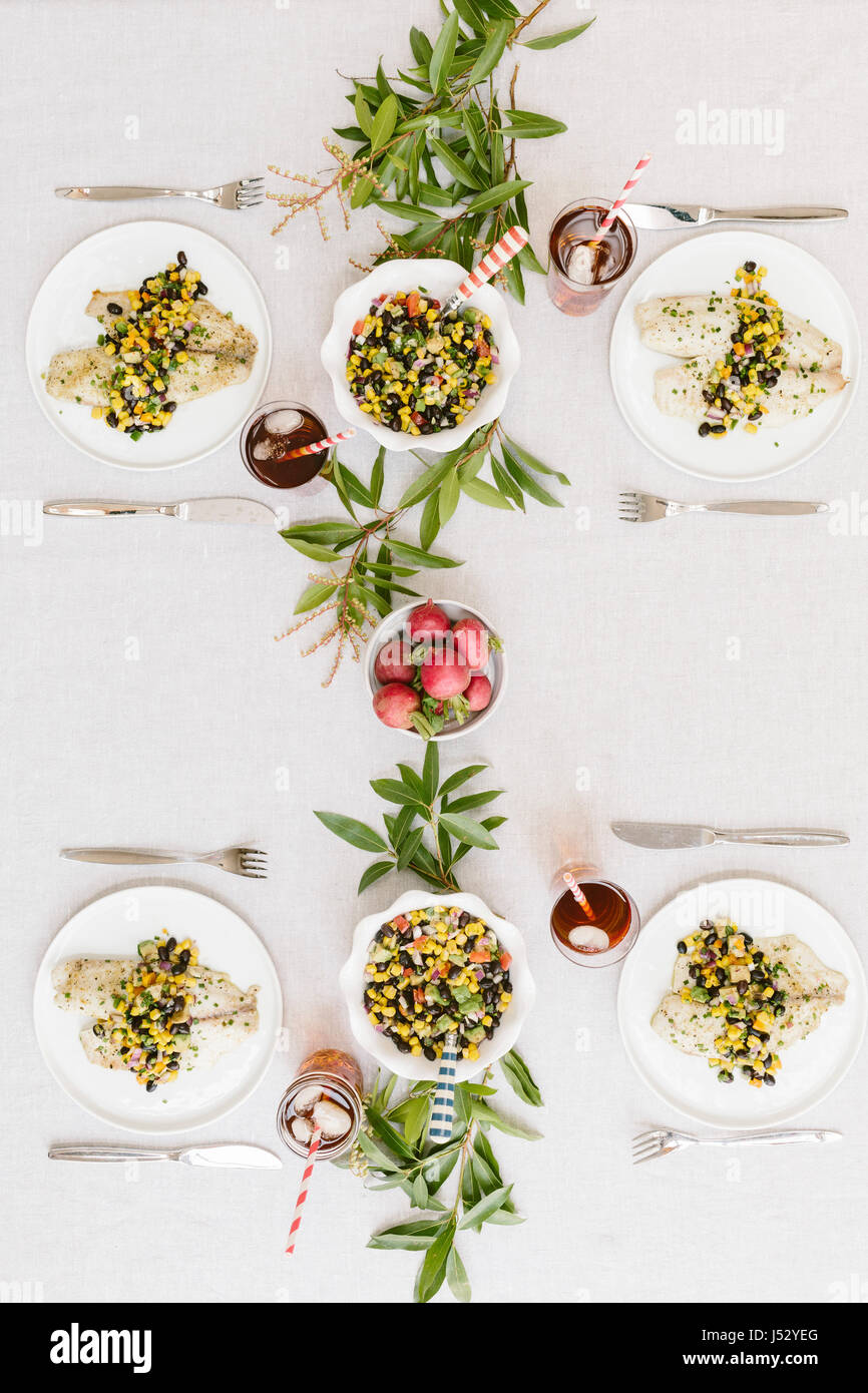 A summery (happy & bright) tablesetting with a portion of Baked Lime and Olive oil tilapia with black bean salsa - Stock Image