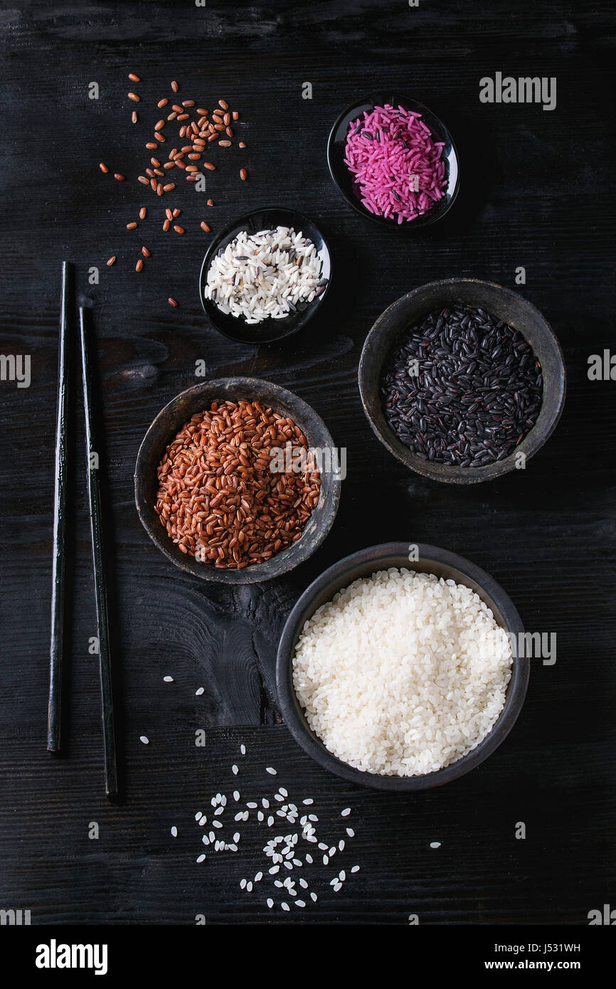 Variety assortment of raw uncooked colorful rice white, black, brown, pink in black bowls over burnt wooden background - Stock Image