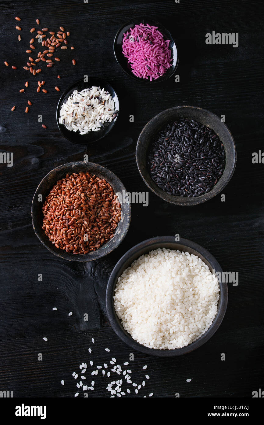 Variety assortment of raw uncooked colorful rice white, black, brown, pink in black bowls over burnt wooden background. - Stock Image