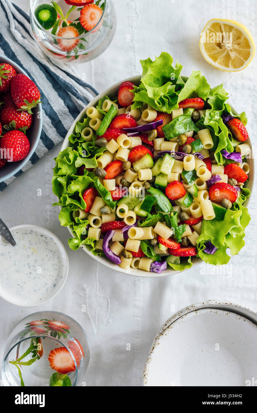 Strawberry Pasta Salad with herbs and cucumber in a bowl and accompanied by two glass of flavored water and bowls. - Stock Image
