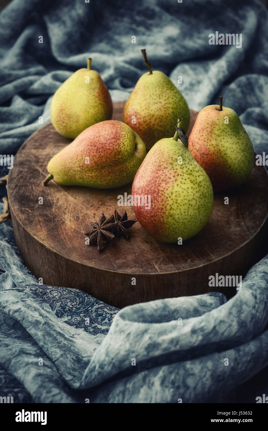 Five pears on a chopping board with rustic setup and styling. - Stock Image