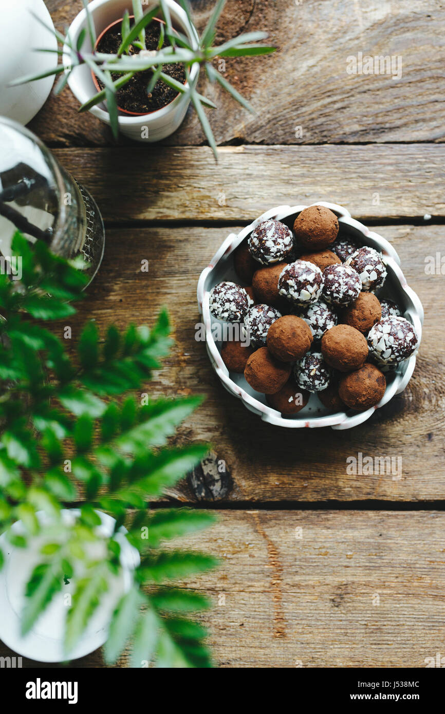 Chocolate truffles covered in nuts, on a wooden table. - Stock Image