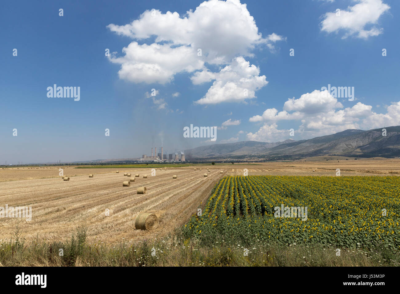 Harvested Field With Straw Bales and a Greek Public Power Company plant in Ptolemaida, Greece. - Stock Image