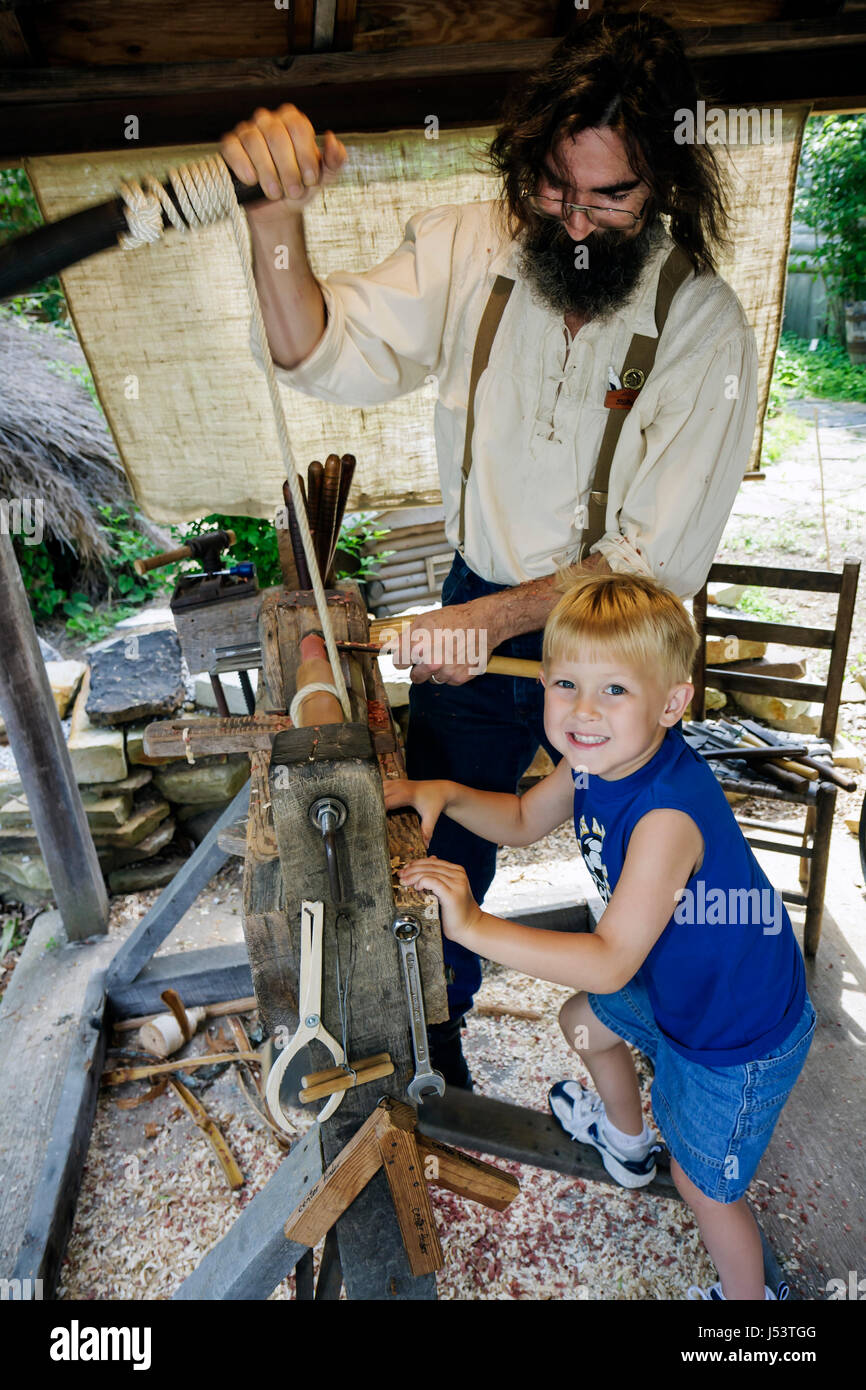 Arkansas Ozark Mountains Mountain View Ozark Folk Center State Park Foot Lathe man beard boy learn hands on tradition - Stock Image